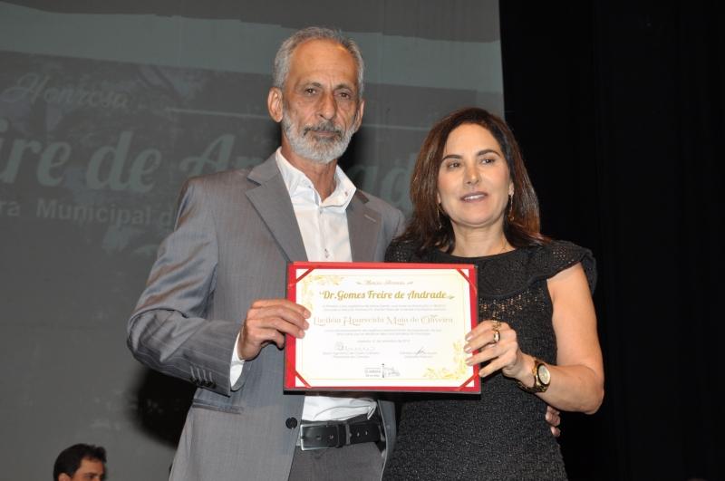 Geraldo Sales de Souza entrega a comenda a sua homenageada.