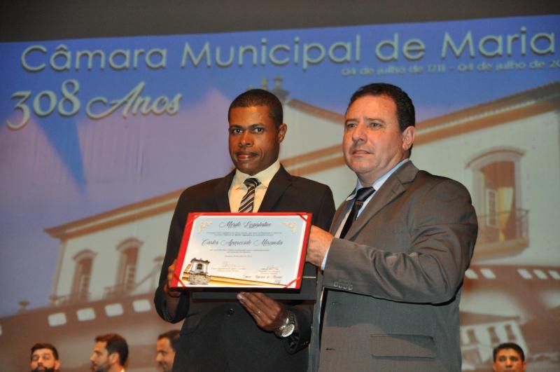 Carlos Miranda recebe o Mérito Legislativo pelas mãos do vereador Adimar José Cota (PSC).