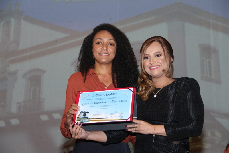 Letícia Aparecida de Matos Oliveira recebe o Mérito Legislativo pelas mãos da vereadora Daniely Souza Alves (PR).