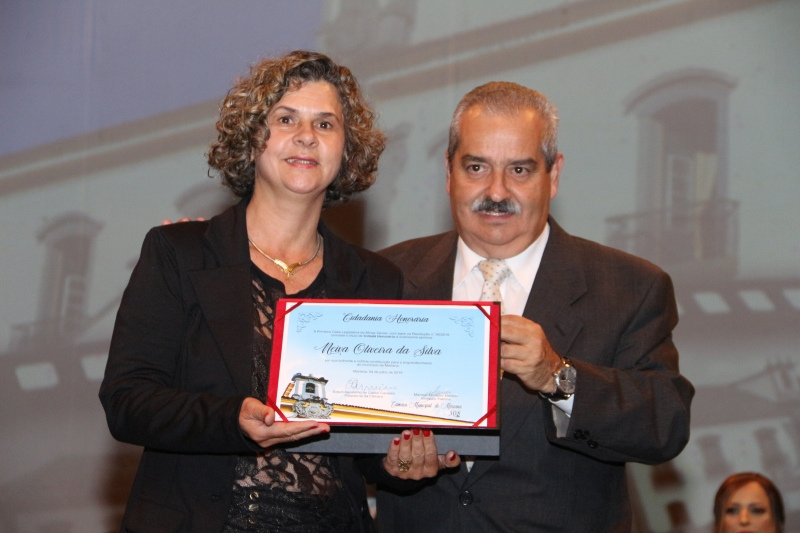 O vereador Marcelo Macedo (PSDB) entrega a Neiva Oliveira o título de Cidadania Honorária.